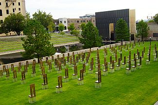Oklahoma_City_National_Memorial_viewed_from_the_south_showing_the_memorial_chairs,_Gate_of_Time,_Reflecting_Pool,_and_Survivor_Tree